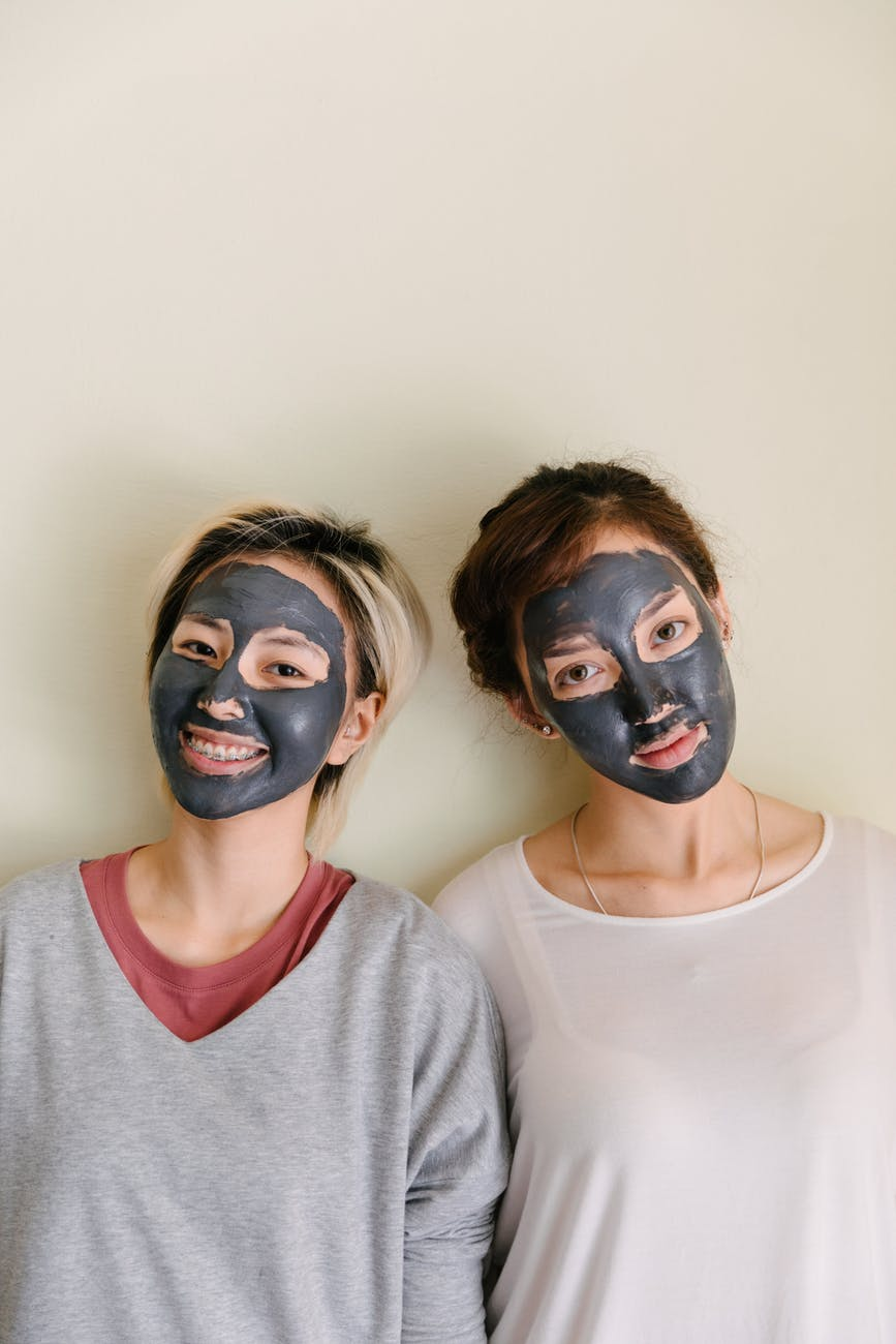 multiethnic women with black facial mask on beige background