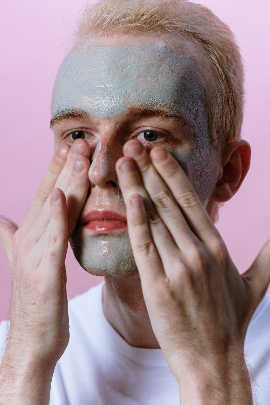 man in white shirt covering his face with his hand